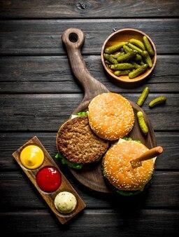 Burger auf schneidebrett mit einem messer und essiggurken in einer schüssel auf schwarzem holztisch