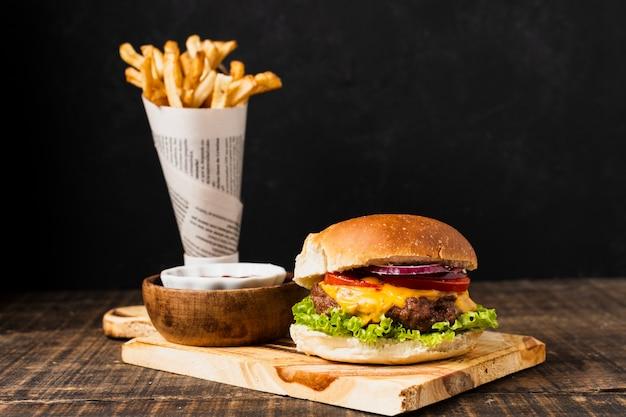 Burger auf schneidebrett mit pommes frites