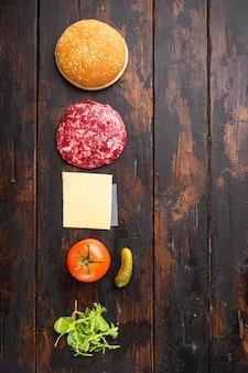 Burger-banner. rohe zutaten für burger-set, auf alten dunklen holztisch