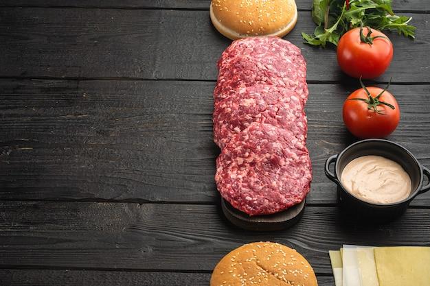 Burger-banner. rohe zutaten für burger-set, auf schwarzem holztisch