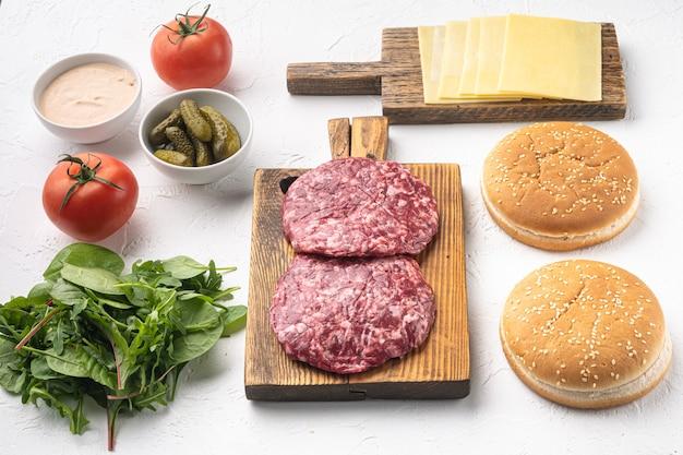 Burger-banner. rohe zutaten für burger-set, auf weißem stein