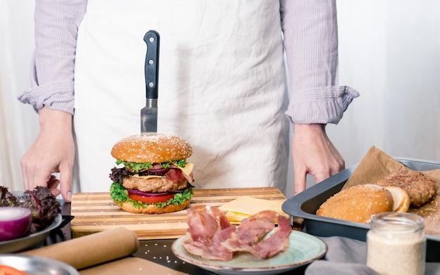 Burger cheeseburger hamburger großer chif koch, der weißen hintergrund nach hause kocht