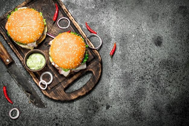 Burger des frischen rindfleischs mit einem messer auf dem brett auf einem rustikalen hintergrund