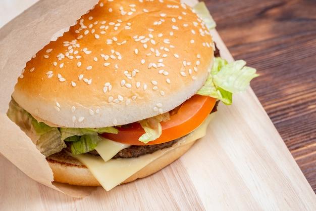 Burger in papier draufsicht von der seite auf einem hölzernen hintergrund.