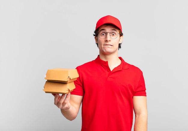 Burger liefern jungen, die verwirrt und verwirrt aussehen, sich mit einer nervösen geste auf die lippe beißen und die antwort auf das problem nicht kennen