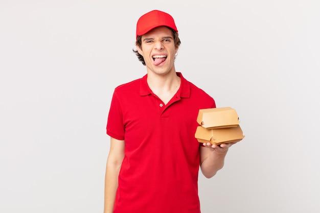 Burger liefern mann mit fröhlicher und rebellischer einstellung, scherzen und strecken die zunge heraus
