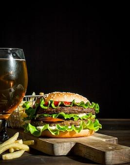 Burger mit bier in einem glas und pommes auf holztisch