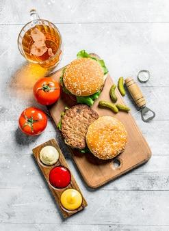 Burger mit bier, tomaten und verschiedenen saucen. auf weißem hölzernem hintergrund