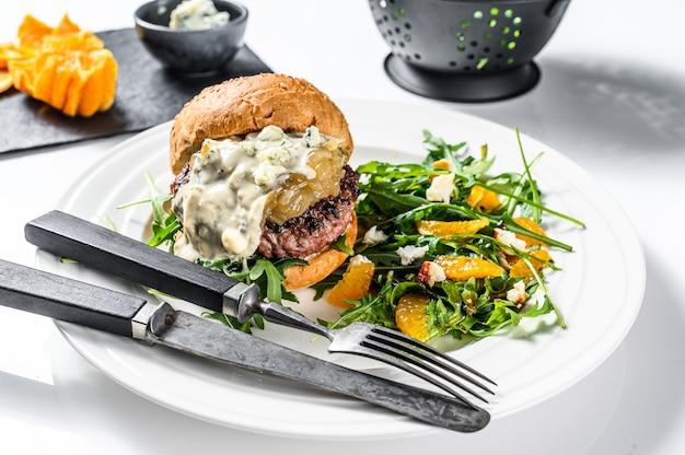 Burger mit blauschimmelkäse, marmorrindfleisch und zwiebelmarmelade, eine beilage aus salat mit rucola und orangen. weißer hintergrund. draufsicht