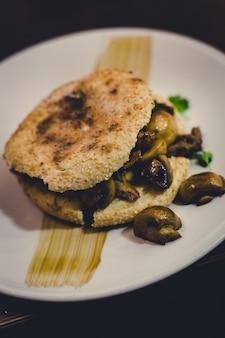 Burger mit champignons und hühnchen auf einem teller