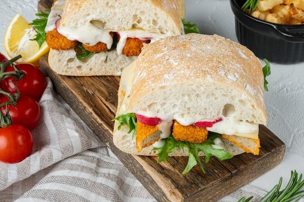 Burger mit fischstäbchen frische salattomate und tartarsauce auf holzschneidebrett gesetzt
