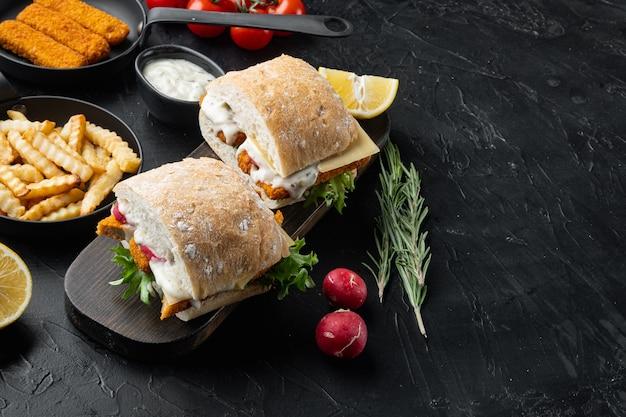 Burger mit fischstäbchen frische salattomate und tartarsauce auf holzschnitt gesetzt