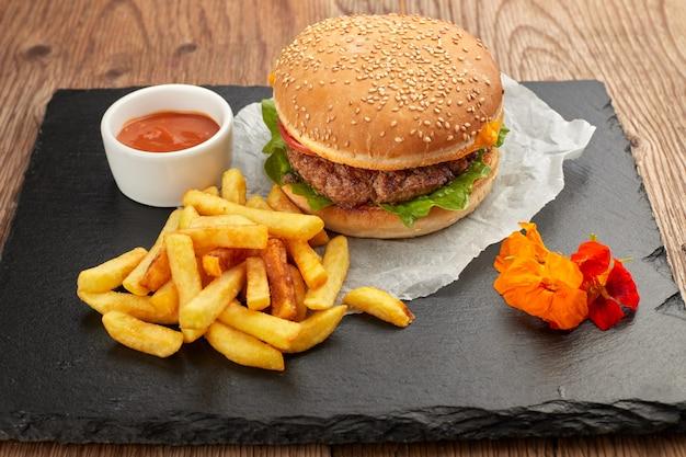 Burger mit fleisch und kartoffeln auf schwarzem schiefer