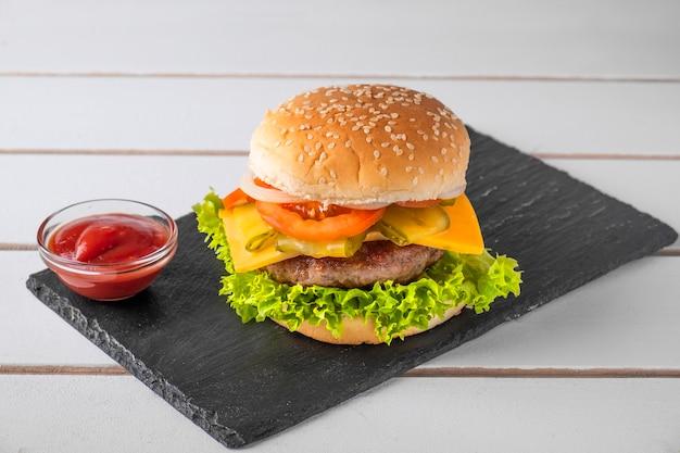 Burger mit fleischkotelett, gelbem käse, zwiebel, tomate und kopfsalat.