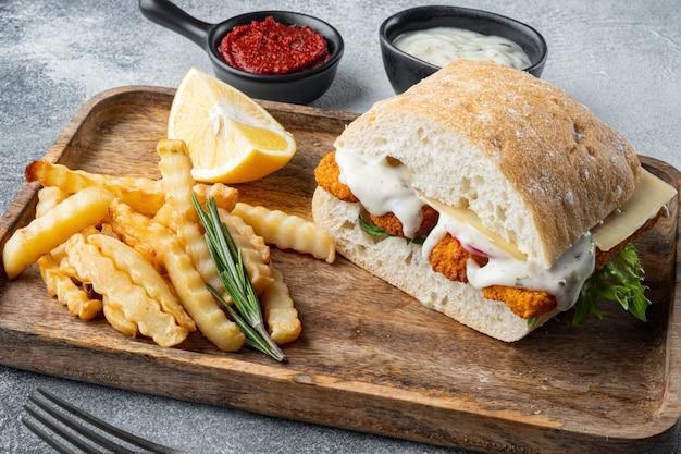 Burger mit frischen salattomaten- und tartarsauce der fischstäbchen auf grauem hintergrund
