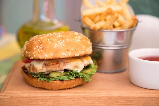 Burger mit hühnerkotelett und pommes