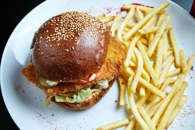 Burger mit hühnerschnitzel, tomaten, gurken und salat mit einer beilage aus pommes frites auf einem weißen teller. leckerer chickenburger. selektiver fokus. fast food