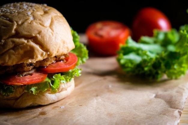 Burger mit käse, salaten und gemüse auf einer schwarzen fläche