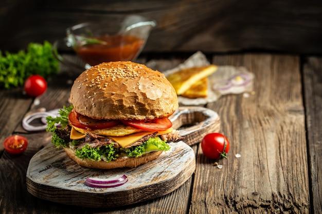 Burger mit kartoffelpuffer und fleisch auf hölzernem weinlese-tisch.