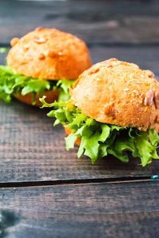 Burger mit kopfsalat auf rustikalem holztisch