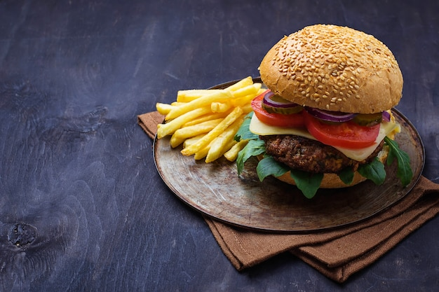 Burger mit kotelett, tomaten, käse und pommes frites