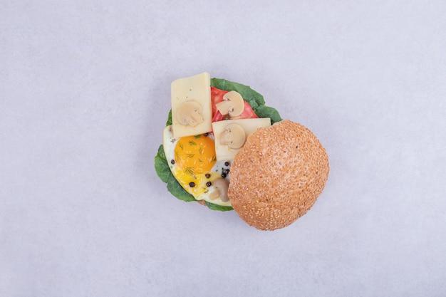 Burger mit omelett, tomaten, pilzen und zwiebeln auf weißer oberfläche.