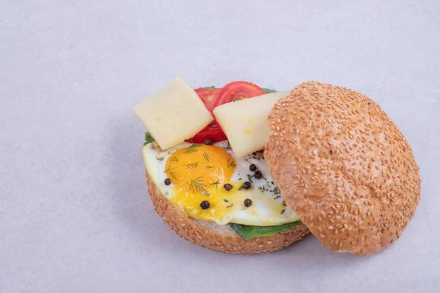 Burger mit omelett, tomaten, pilzen und zwiebeln.