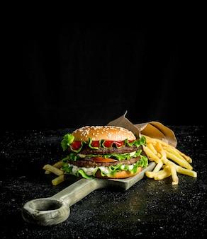 Burger mit pommes auf dem schneidebrett. auf schwarzem rustikalem hintergrund