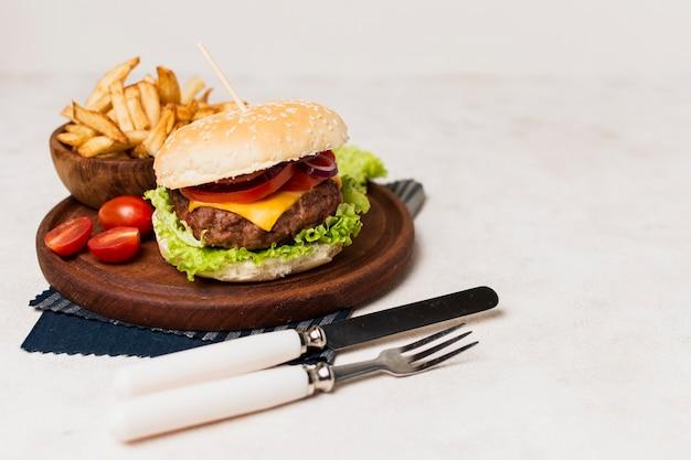 Burger mit pommes frites und besteck