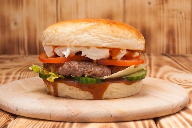 Burger mit rinderpatty, gurken, tomaten und frischkäse