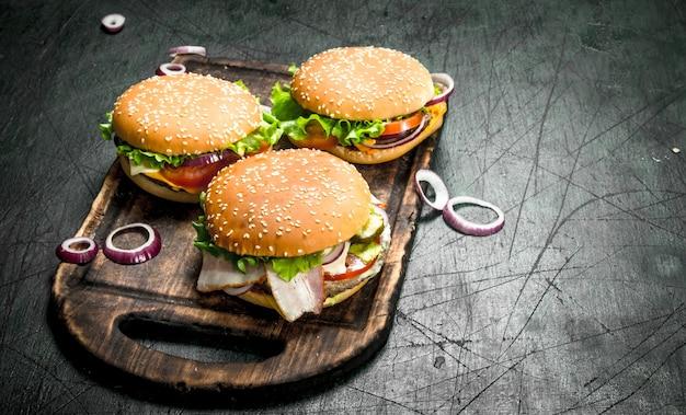 Burger mit rindfleisch, gemüse und süßen zwiebeln auf einem alten brett auf einem rustikalen hintergrund