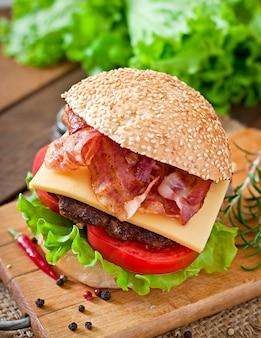 Burger mit rindfleisch, käse, tomate und gebratenem speck