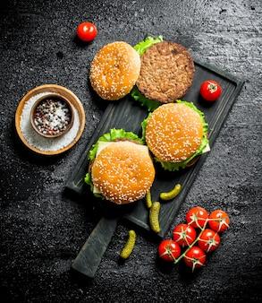 Burger mit rindfleisch und gewürzen in der schüssel. auf schwarzem rustikalem hintergrund