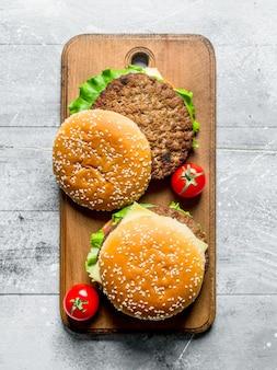 Burger mit saftigem rindfleisch und tomaten auf rustikalem tisch