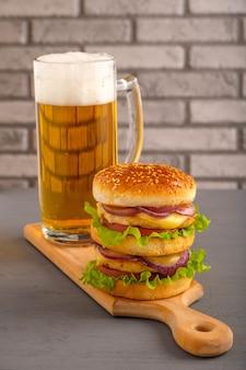 Burger mit schnitzel, cheddar, bruststück, eingelegten zwiebeln, salat, gegrillter sauce und grill