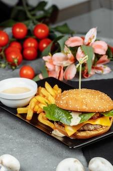 Burger mit schnitzel, käse und tomaten. mit pommes frites und burgersauce.