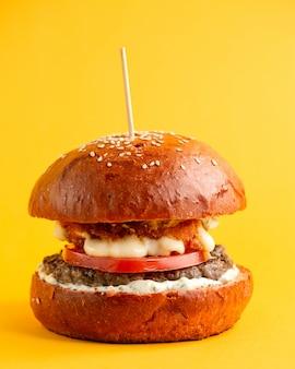 Burger mit tomaten-rindfleisch-pastetchen gegrilltem käse und sauce in burgerbrötchen