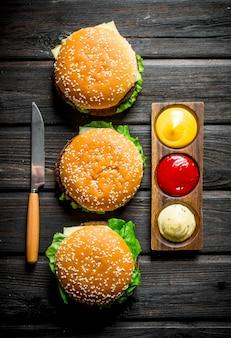 Burger mit verschiedenen saucen und einem messer auf schwarzem holztisch
