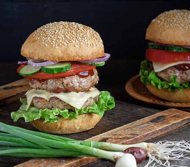 Burger mit zwei gebratenen schnitzel, käse und gemüse