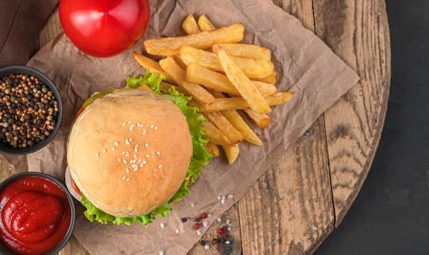 Burger, pommes frites und soße auf einem holzbrett. ansicht von oben. fastfood.