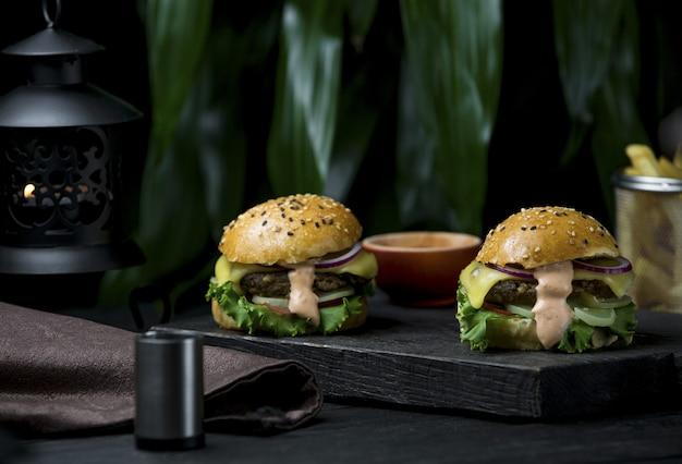 Burger pro zwei personen mit geschmolzenem käse auf einem schwarzen brett