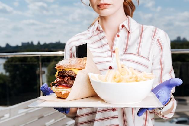 Burger und kartoffeln. junge kellnerin, die gestreiftes hemd mit burger und bratkartoffeln für kunden trägt