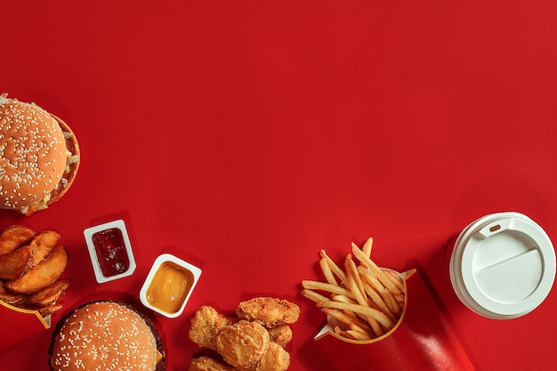 Burger und pommes frites hamburger und pommes frites in roter pappschachtel fast food auf rotem hintergrund
