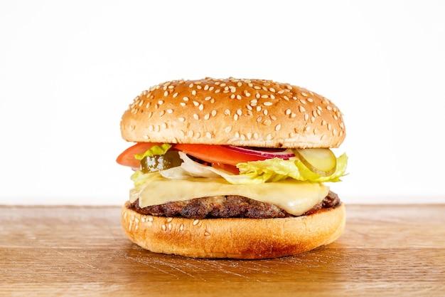Burger volles gesicht mit gemüse, gewürzen und pommes. fleischhamburger, weißer hintergrund