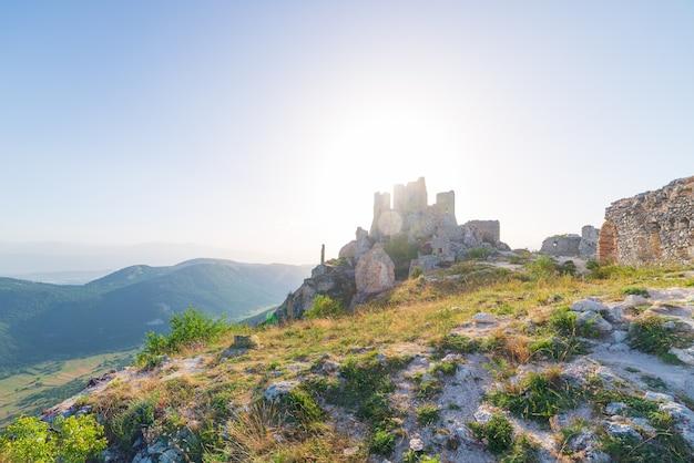 Burgruine auf berggipfel bei rocca calascio, italienisches reiseziel, wahrzeichen im nationalpark gran sasso, abruzzen, italien. die sonne des klaren blauen himmels platzte im gegenlicht