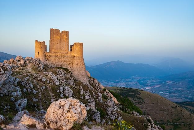 Burgruine auf berggipfel bei rocca calascio, italienisches reiseziel, wahrzeichen im nationalpark gran sasso, abruzzen, italien. strahlend blauer himmel in der abenddämmerung