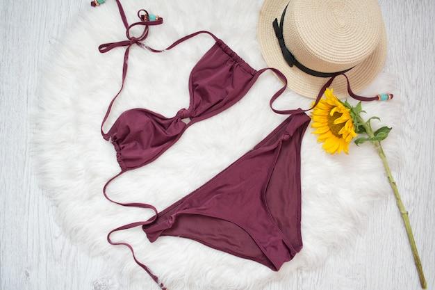 Burgunder badeanzug, strohhut und sonnenblume. weißes fell auf der, ansicht von oben