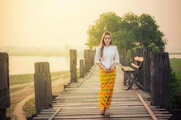 Burmesische frau, die auf u-bein-brücke geht