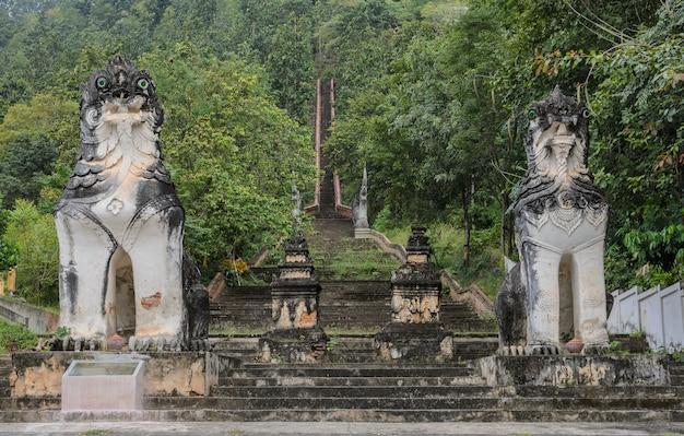 Burmesische gemeißelte löwenstatue an den treppen, die zum hügel am wat phra non in mae hong son, thailand führen