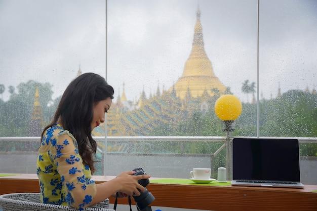 Burmesische weibliche touristen sitzen und entspannen sich und spielen ein notebook und eine kamera im raum mit blick auf die wunderschöne shwedagon-pagode.